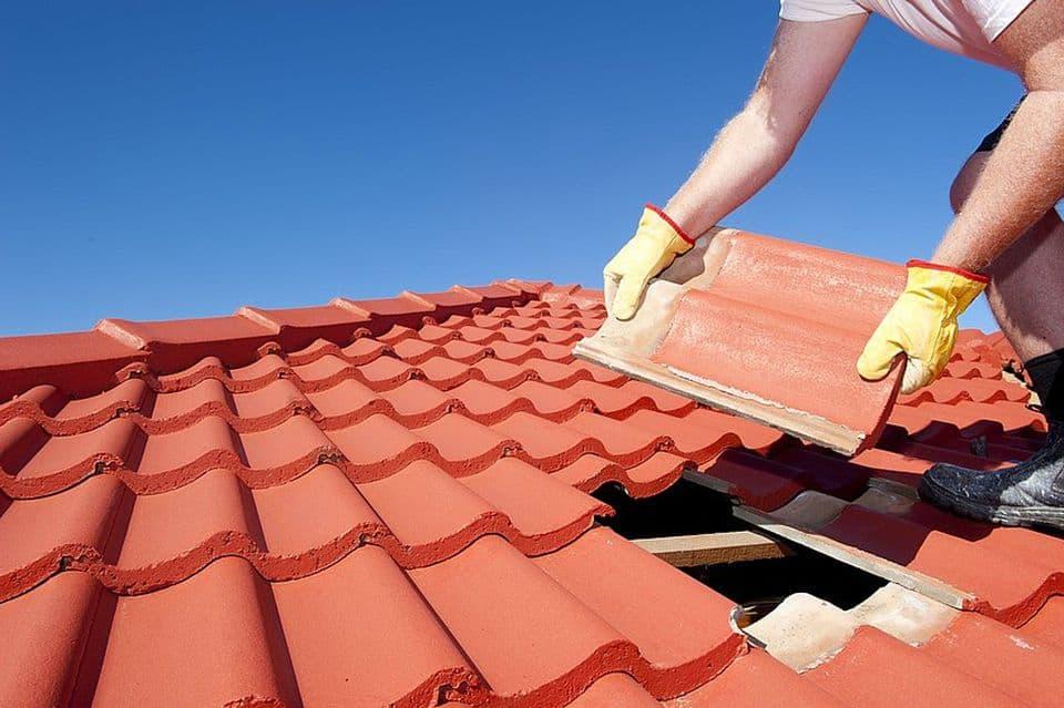guy working on clay shingle roof